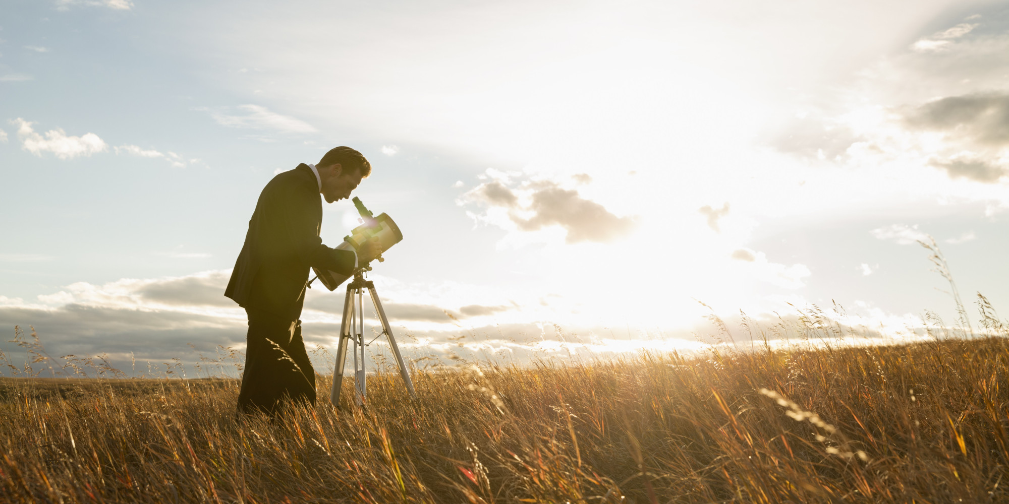 Businessman using telescope on field