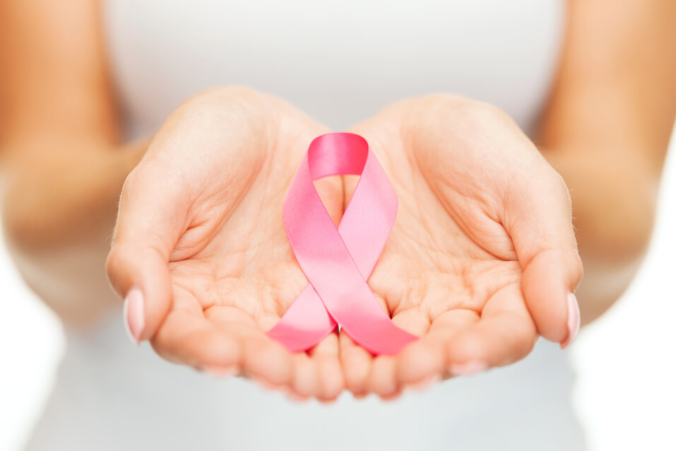 healthcare and medicine concept - womans hands holding pink breast cancer awareness ribbon
